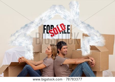 Happy couple sitting on floor after buying house against house outline in clouds
