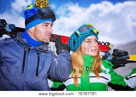 Handsome man and beautiful woman enjoying alpine ski resort, portrait of a nice couple playing winter sports, active lifestyle people, family travel to Europe on Christmas holidays