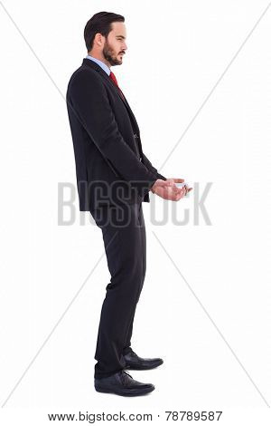 Unsmiling businessman holding something with his hands on white background