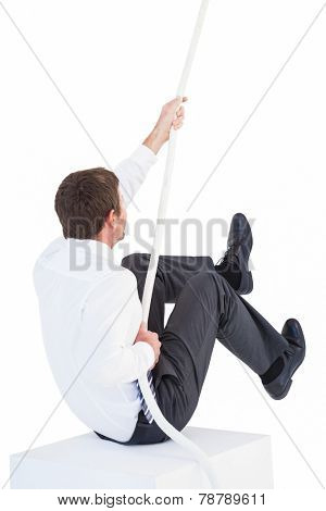 Businessman pulling a rope with effort on white background