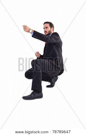 Businessman pulling something with effort on white background