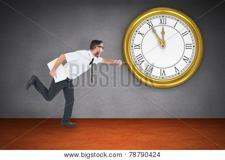 Geeky young businessman running late against room with wooden floor