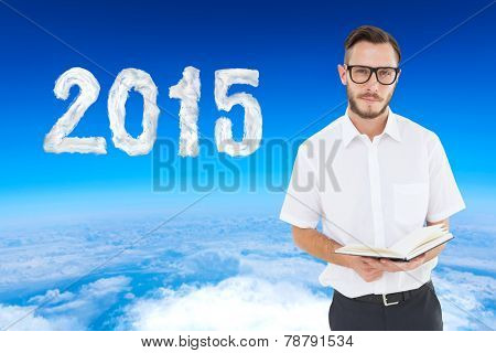 Geeky young man reading from black book against blue sky over white clouds