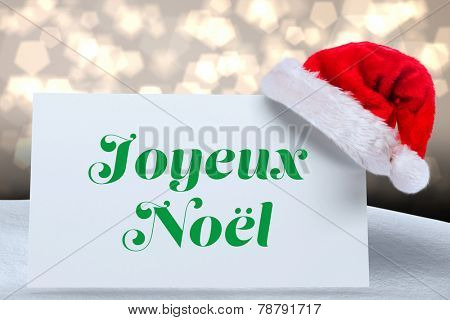 Joyeux noel against shimmering light design over boards