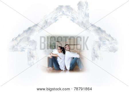 Glowing couple sitting on the floor against house outline in clouds