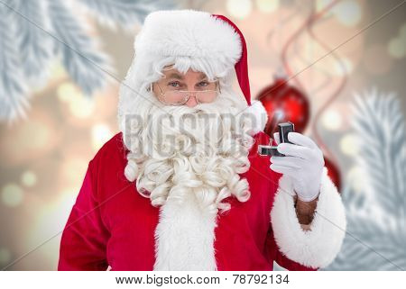 Cheerful santa holding a jewelry box against digital hanging christmas bauble decoration