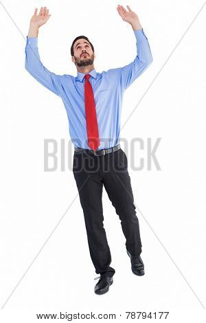 Businessman in suit pushing up with effort on white background