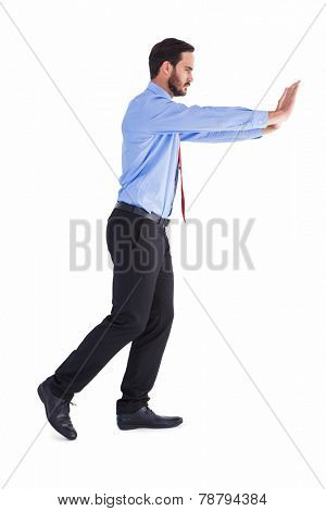 Businessman in suit pushing with effort on white background