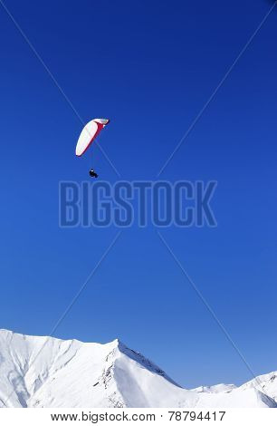 Paraglider In Snowy Mountains At Nice Sun Day