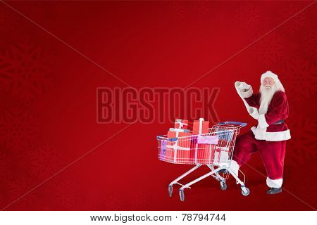 Santa pushes a shopping cart while reading against red background