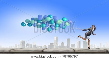 Young businesswoman with bunch of balloons running in a hurry