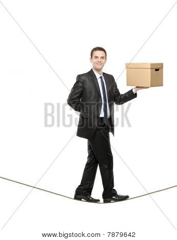 A businessman holding a paper box and walking on a rope