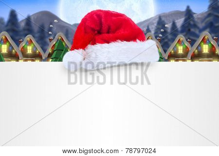Santa hat on poster against quaint town with bright moon