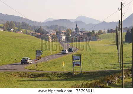 Cars pass by a countryside road, Affoltern im Emmental, Switzerland.