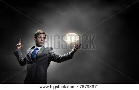 Young thoughtful businessman and human brain above his head