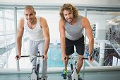 pic of exercise bike  - Portrait of fit young men working on exercise bikes at the gym - JPG