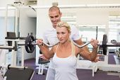 stock photo of personal care  - Personal male trainer helping young woman with lifting barbell in the gym - JPG