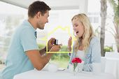 picture of marriage proposal  - Man proposing marriage to his shocked blonde girlfriend against house outline - JPG