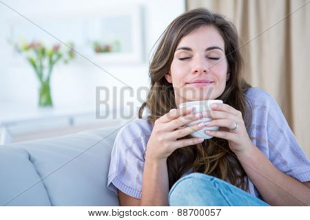 Peaceful woman holding cup of coffee at home in the living room
