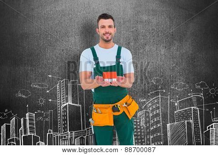Happy construction worker holding house model against hand drawn city plan