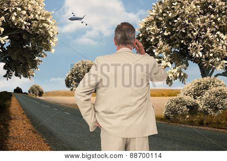 Thinking businessman against road leading out to the horizon