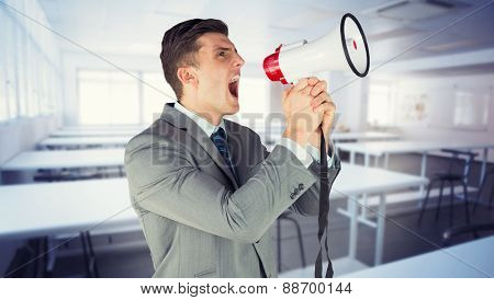 Businessman with megaphone against empty class room