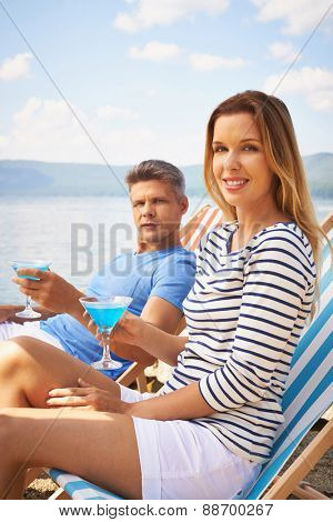 Attractive couple with martini spending summer vacation at resort