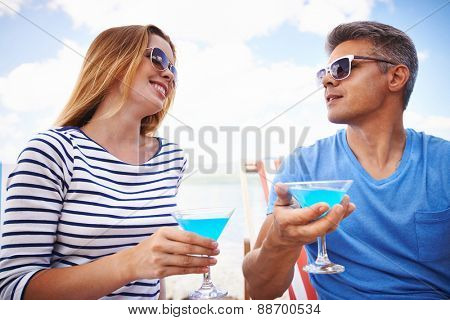 Young couple in eyeglasses toasting with martini during summer vacations