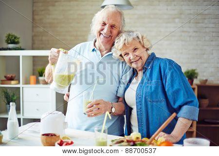 Cheerful seniors having fresh smoothie in the kitchen