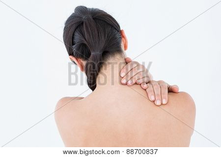 Brunette touching her painful neck on white background