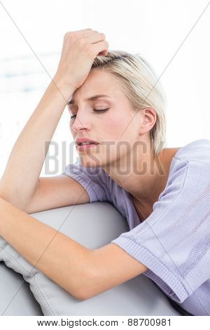 Thoughtful blonde woman sitting on the couch in the living room