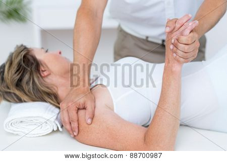 Doctor bending his patient arm in medical office