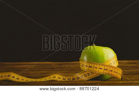 Green apple with measuring tape on wooden background