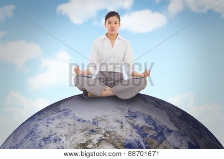Businesswoman sitting in lotus pose against blue sky