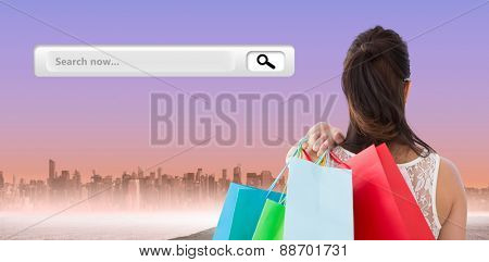Rear view of brunette holding shopping bags against city on the horizon