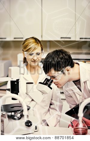 Science and medical graphic against scientists holding clipboard and looking through a microscope