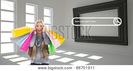 Blonde in winter clothes holding shopping bags against dark white room with frame at wall