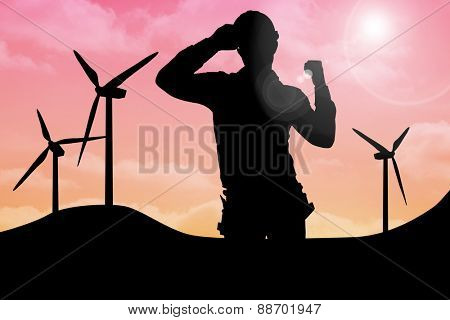 Smiling manual worker clenching fist against sky and mountains