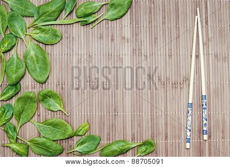 Spinach Leaves On A Bamboo Mat And Bamboo Chopsticks