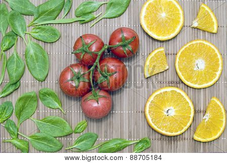 Spinach Leaves, Orange Slice, A Bunch Of Tomatoes On A Bamboo Mat