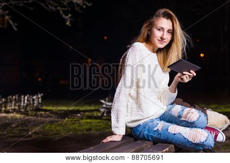 Young woman sitting with Tablet and reading