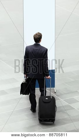 businessman who chooses in front of a sign with suitcase and trolley