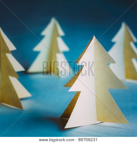 White Christmas Trees Made Of Old Paper On Blue Background.