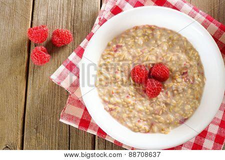 Breakfast oatmeal with raspberries overhead view