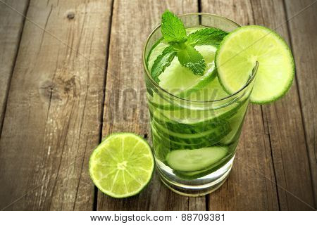 Healthy lime and cucumber water against wood