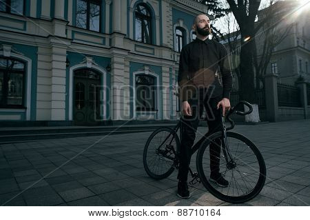 guy in black clothes stands with fix bike