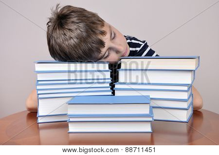 Tired young boy and books