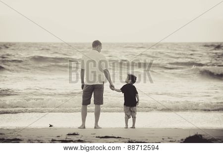 Happy Father Holding Holding Hand Of Little Son Walking Together On The Beach With Barefoot