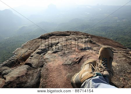 hiker legs relax at mountain peak cliff