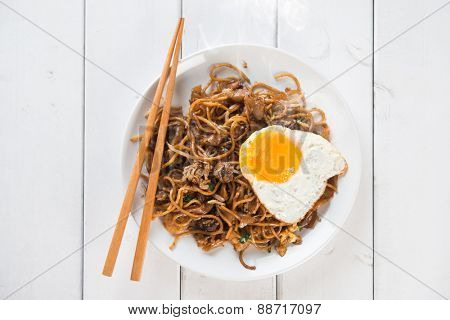 Stir fried char kuey teow with prawns and chopstick over wooden background.